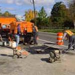 Public Works employees paving a street.